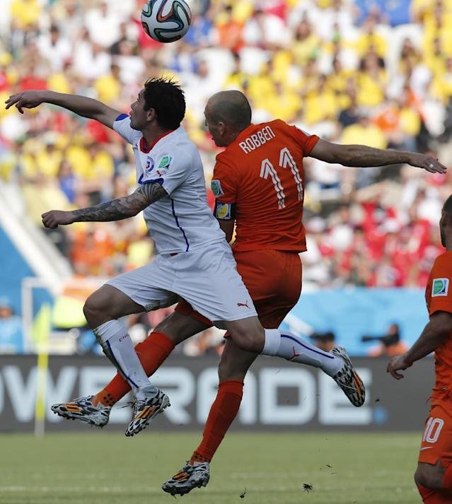 Chile's Eugenio Mena, left, and Netherlands' Arjen Robben go for a header during the group B World Cup soccer match between the Netherlands and Chile at the Itaquerao Stadium in Sao Paulo, Brazil, Monday, June 23, 2014. (AP Photo/Frank Augstein)