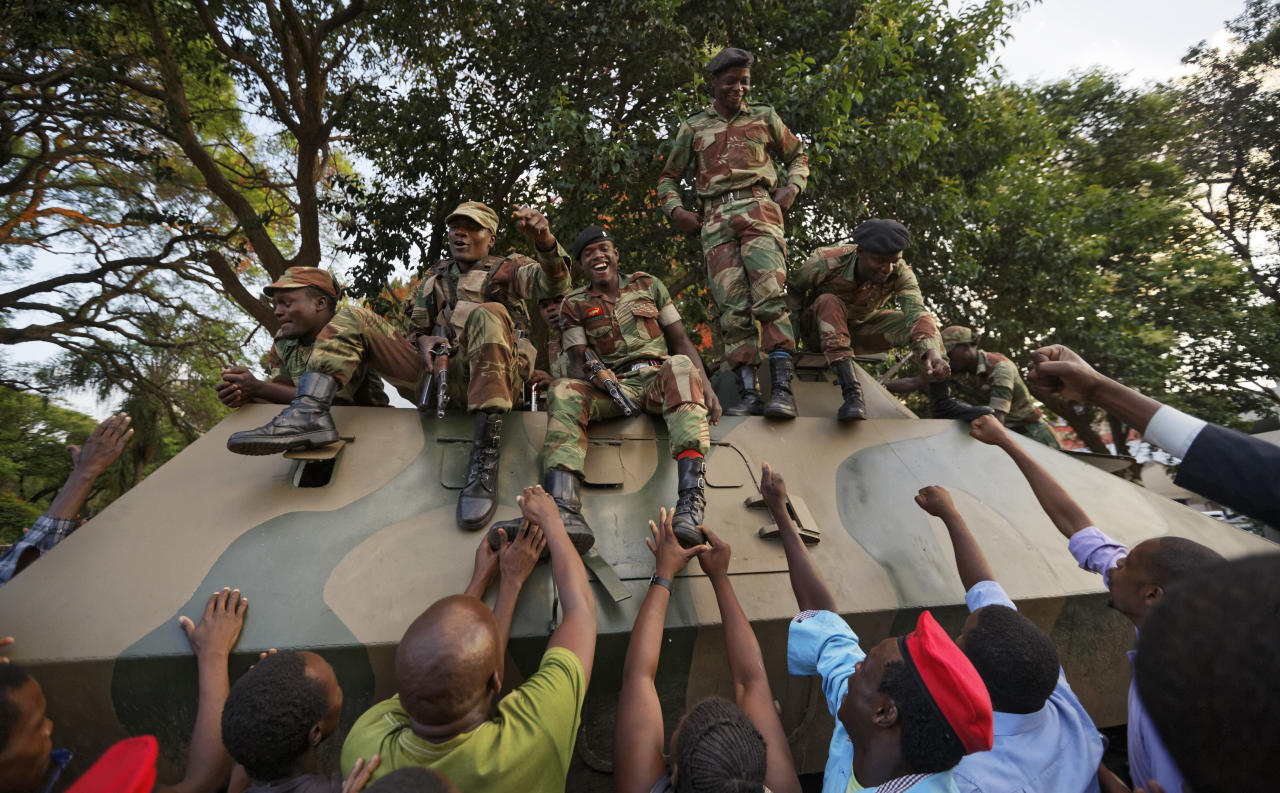 <p>Zimbabweans reach out to touch and thank army soldiers, as they celebrate outside the parliament building immediately after hearing the news that President Robert Mugabe had resigned, in downtown Harare, Zimbabwe Tuesday, Nov. 21, 2017. (Photo: Ben Curtis/AP) </p>