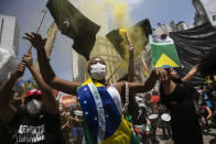 A woman, wrapped in a Brazilian national flag, chats slogans during a protest against Brazilian President Jair Bolsonaro calling for his impeachment over his government's handling of the pandemic and accusations of corruption in the purchases of COVID-19 vaccines, in Rio de Janeiro, Brazil, Saturday, Oct. 2, 2021. (AP Photo/Bruna Prado)