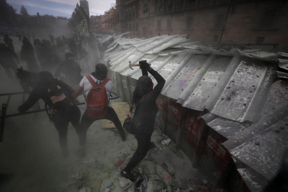 Demonstrators attack a barricade protecting Mexico City's National Palace during a march to commemorate International Women's Day and to protest against gender violence, Monday, March 8, 2021. (AP Photo/Rebecca Blackwell)