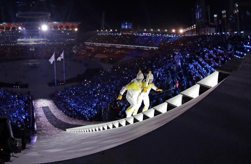 <p>North Korea's Jong Su Hyon, left, and South Korea's Park Jong-ah carry the torch during the opening ceremony of the 2018 Winter Olympics in Pyeongchang, South Korea, Friday, Feb. 9, 2018. (AP Photo/David J. Phillip,Pool) </p>