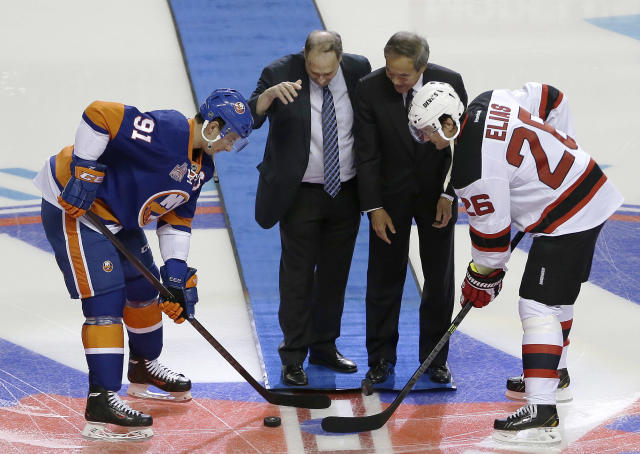New York Islanders center John Tavares, left, and New Jersey Devils left wing Patrik Elias, right, look on as Barclays Center majority owner Bruce Ratner, center left, and Islanders owner Charles Wang drop pucks during the ceremonial puck drop before a preseason NHL hockey game, Saturday, Sept. 21, 2013, in New York. The match is the first ever hockey game held at Barclays Center. (AP Photo/Julio Cortez)