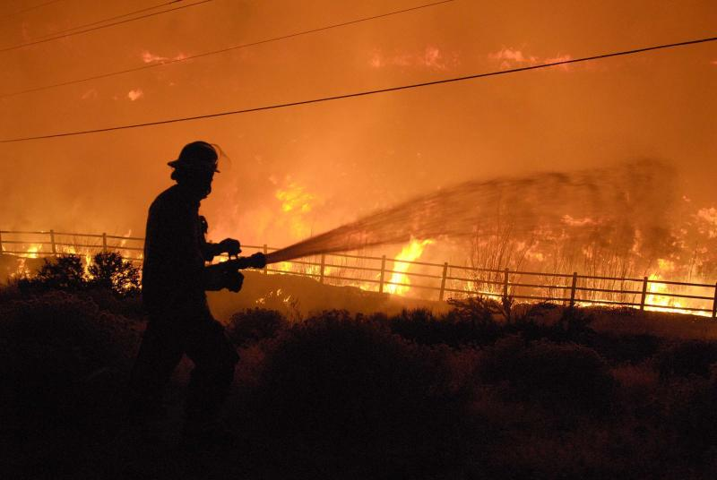 "A firefighter tries to keep back the flames, whipped by strong winds, in Reno, Nev. Friday, Nov. 18, 2011.   Nevada firefighters  are battling a wind-whipped wildfire that has already burned several homes and caused several injuries. Reno Fire Chief Michael Hernandez sayfire crews are having a tough time ""getting ahead of"" the 400-acre blaze.  He also says flames broke off into two areas in Caughlin Ranch.  Hernandez says about a dozen homes have burned.   (AP Photo/The Reno Gazette-Journal,  Tim Dunn) NEVADA APPEAL OUT;  NO SALES"