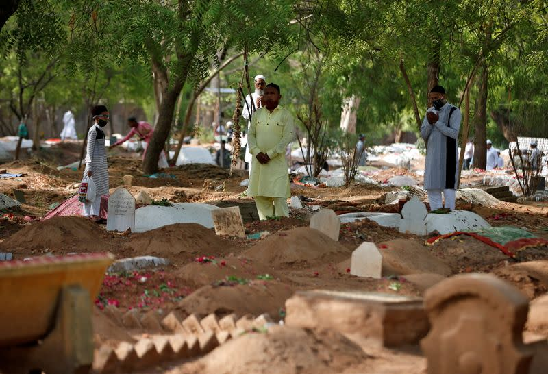 Muslims pray next to the graves of their relatives including those who died from the coronavirus disease (COVID-19), on the occasion of the Eid al-Fitr amidst the spread of the disease in Ahmedabad