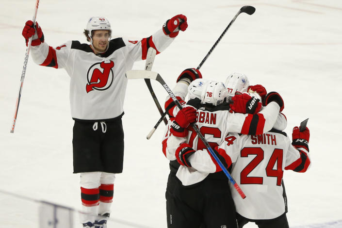 New Jersey Devils players celebrate a goal by defenseman Ty Smith (24) during the second period of an NHL hockey game against the Buffalo Sabres, Saturday, Jan. 30, 2021, in Buffalo, N.Y. (AP Photo/Jeffrey T. Barnes)