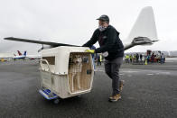 """The first dog brought off after the landing of a """"Paws Across the Pacific"""" pet rescue flight is wheeled across the tarmac Thursday, Oct. 29, 2020, in Seattle. Volunteer organizations flew more than 600 dogs and cats from shelters across Hawaii to the U.S. mainland, calling it the largest pet rescue ever. The animals are being taken from overcrowded facilities in the islands to shelters in Washington state, Oregon, Idaho, and Montana. (AP Photo/Elaine Thompson)"""