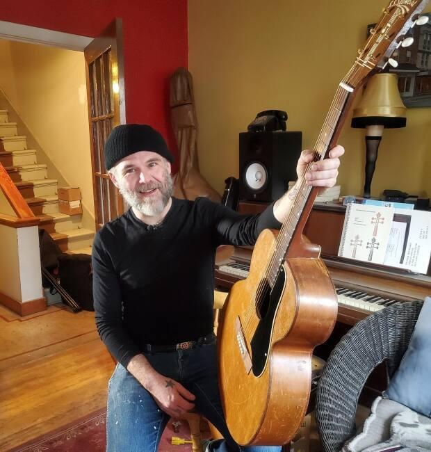Chris Kearsey holds a guitar originally purchased at O'Brien's Music in the 1950s that was reacquired and restored at the shop.