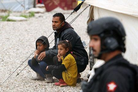 Displaced Iraqi sit outside their tent during the visit of UN Secretary General Guterres at Hasansham camp, in Khazer
