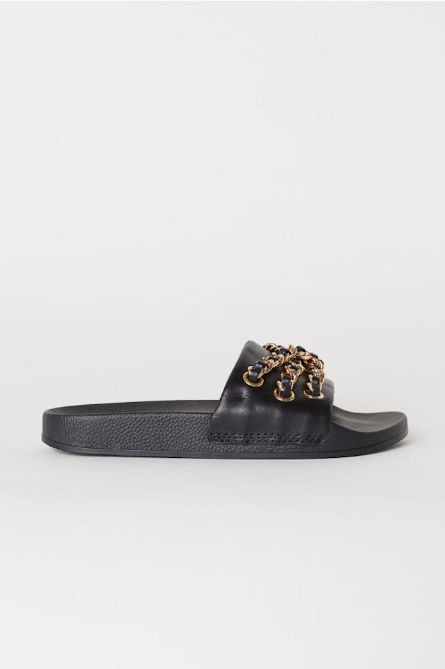 """<p>Made of faux-leather, these slides feature gold-plated chains on top. Wear these by the pool or at the beach and you'll be the envy of everyone around.<br /><a rel=""""nofollow"""" href=""""https://fave.co/2OAnedo"""">Shop it</a>: H&M x Moschino faux-leather slides, $99,<a rel=""""nofollow"""" href=""""https://fave.co/2OAnedo""""> hm.com</a> </p>"""