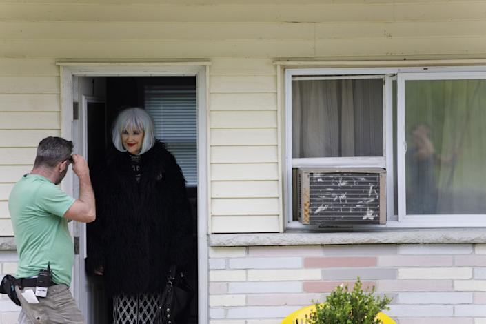 """Catherine O'Hara peers out of a doorway between takes on the set of """"Schitt's Creek."""""""