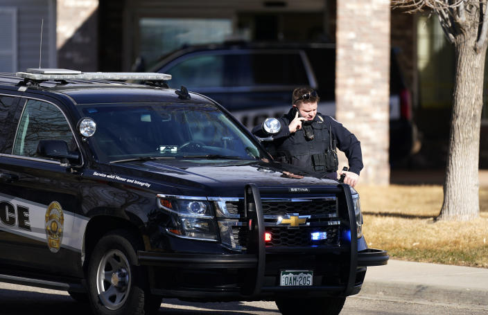 A police officer talks on a mobile device outside the Legacy Assisted Living at Lafayette care facility, Wednesday, Feb. 3, 2021, in Lafayette, Colo. A 95-year-old resident of the assisted care home was taken into police custody Wednesday after allegedly shooting an employee at the center. (AP Photo/David Zalubowski)