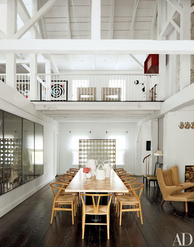 """In <a rel=""""nofollow"""" href=""""http://www.architecturaldigest.com/story/india-mahdavi-litchfield-county-connecticut-home-article?mbid=synd_yahoo_rss"""">the same home</a>, the double-height formal dining area, also in a former barn, is furnished with chairs designed by Hans J. Wegner for Carl Hansen & Son and a custom-made table by India Mahdavi."""