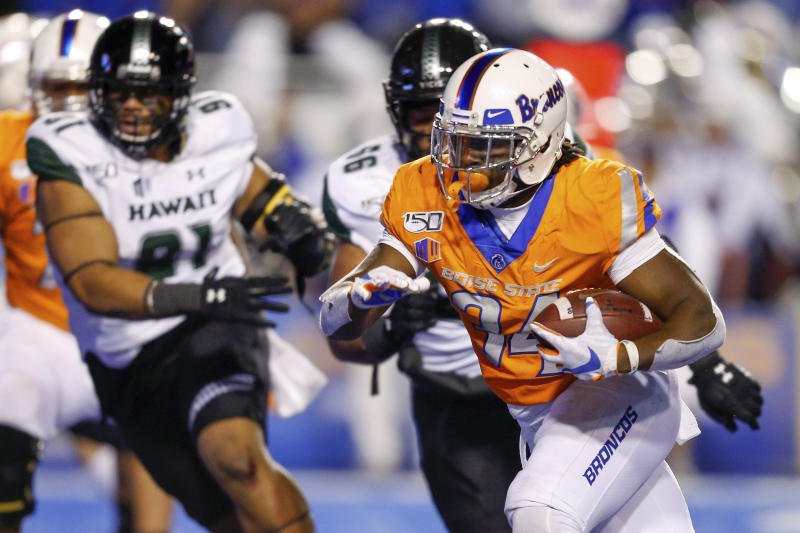 Boise State running back Robert Mahone, right runs past the Hawaii defense for a 13-yard touchdown during the first half of an NCAA college football game Saturday, Oct. 12, 2019, in Boise, Idaho. (AP Photo/Steve Conner)