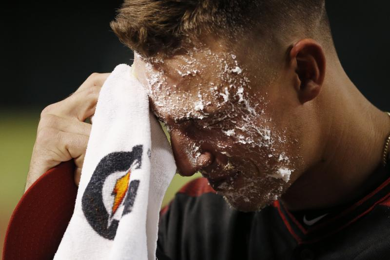 Arizona Diamondbacks' Jake Lamb wipes whipped cream off his face after getting a pie to the face from teammate Adam Jones after a baseball game win against the Miami Marlins, Monday, Sept. 16, 2019, in Phoenix. Lamb delivered a three-run double and the Diamondbacks defeated the Marlins 7-5. (AP Photo/Ross D. Franklin)