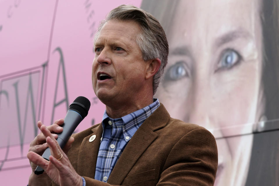 U.S. Rep. Roger Marshall, R-Kan., talks to the crowd in front of photo of Supreme Court nominee Amy Coney Barrett while attending a Concerned Women for America event outside a gun store in Kansas City, Kan. Wednesday, Oct. 21, 2020. Marshall is facing stiff competition from state Sen. Barbara Bollier in the race to fill an open Senate seat in Kansas. (AP Photo/Charlie Riedel)