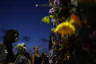 People visit a makeshift memorial for the victims of the Champlain Towers South condo building collapse, as they gather for a multi-faith vigil near the site where the building once stood, on Thursday, July 15, 2021, in Surfside, Fla.(AP Photo/Rebecca Blackwell)