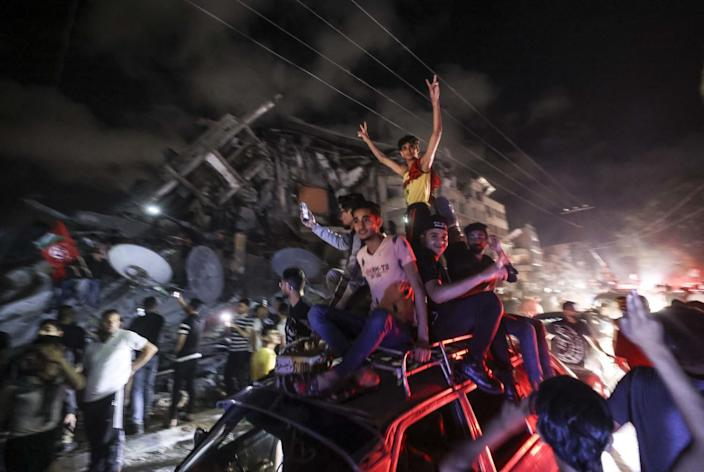 People sit on top of a car as crowds celebrate
