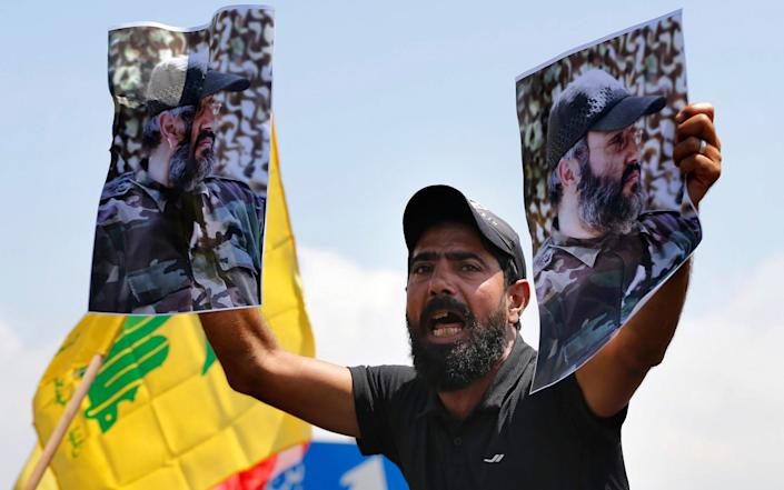 A Hezbollah supporter chant slogans and hold posters of the late Hezbollah military commander Imad Mughniyeh
