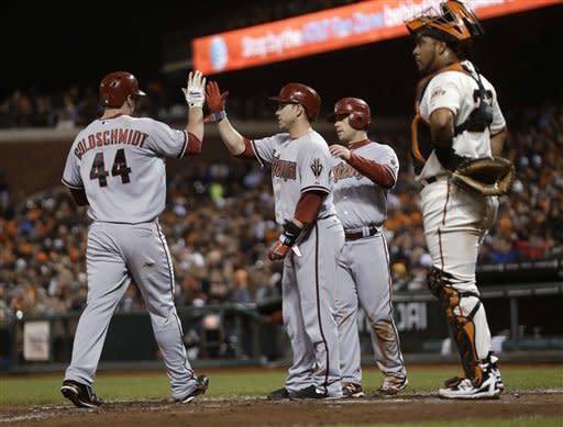 Arizona Diamondbacks' Paul Goldschmidt (44) is met at home plate by teammates Miguel Montero, second from left, and Aaron Hill after Goldschmidt's three-run home run against the San Francisco Giants during the third inning of a baseball game Tuesday, Sept. 25, 2012, in San Francisco. (AP Photo/Marcio Jose Sanchez)