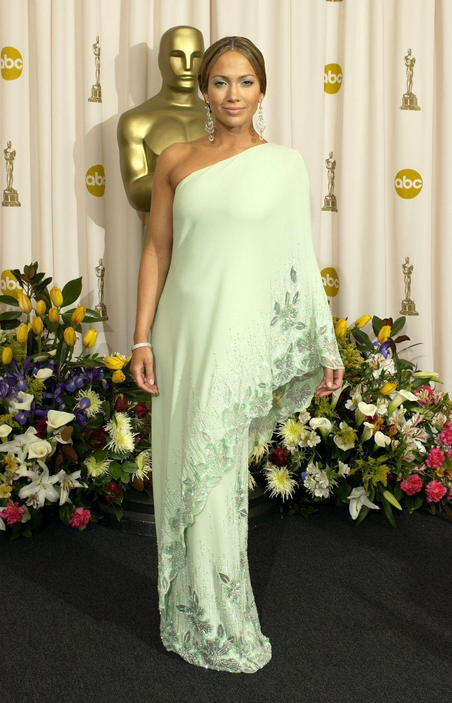 <p>J. Lo killed the red carpet in this mint green one-shoulder Valentino dress with beading at the hem. She attended the awards with her then boyfriend Ben Affleck. (#TBT to <em>Gigli</em>.) </p>