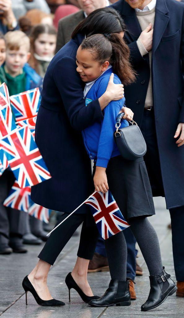 <p>Seriously, Meg is a hugger. Here she is embracing another young fan while out with Prince Harry in March 2018. Now I want a hug. </p>