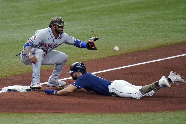 Tampa Bay Rays' Brandon Lowe slides into third base ahead of the throw to New York Mets' Jonathan Villar during the ninth inning of a baseball game Friday, May 14, 2021, in St. Petersburg, Fla. Lowe advanced from first to third base on a single by Willy Adames. (AP Photo/Chris O'Meara)