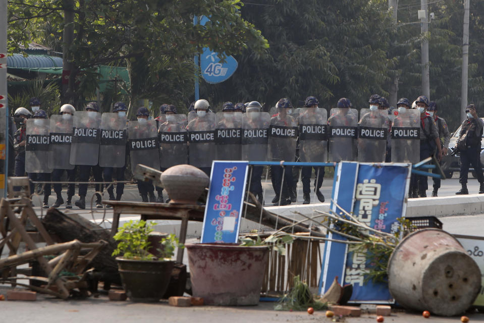 Myanmar riot police with shields move forward during a protest against the military coup in Mandalay, Myanmar, Sunday, Feb. 28, 2021. Police fired tear gas and water cannons and there were reports of gunfire Sunday in Myanmar's largest city Yangon where another anti-coup protest was underway with scores of students and other demonstrators hauled away in police trucks. (AP Photo)