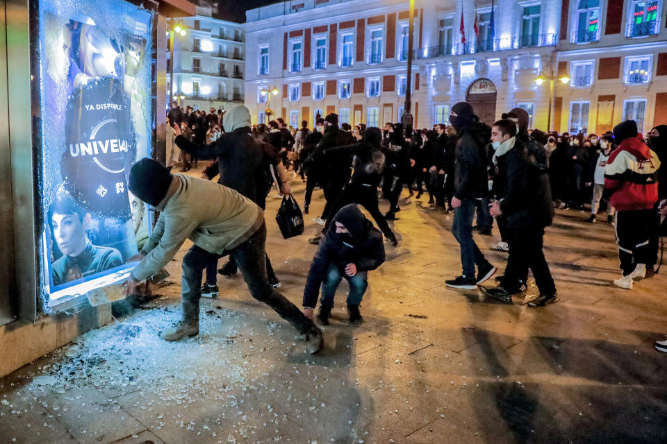 Demonstrators clash with the police following a protest condemning the arrest of rap singer Pablo Hasel in Madrid, Spain, Wednesday, Feb. 17, 2021. Police fired rubber bullets and baton-charged protesters as clashes erupted for a second night in a row Wednesday at demonstrations over the arrest of Spanish rap artist Pablo Hasel. Many protesters threw objects at police and used rubbish containers and overturned motorbikes to block streets in both Madrid and Barcelona. (AP Photo/Manu Fernandez)