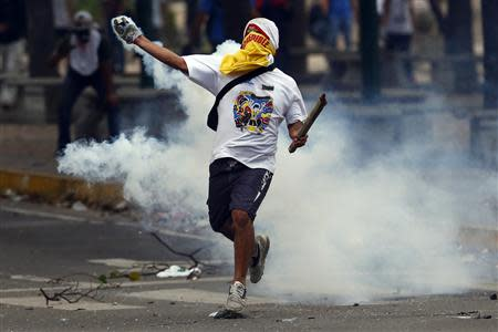 An anti-government protester throws a teargas canister back at the police during a protest at Altamira square in Caracas March 10, 2014. REUTERS/Jorge Silva