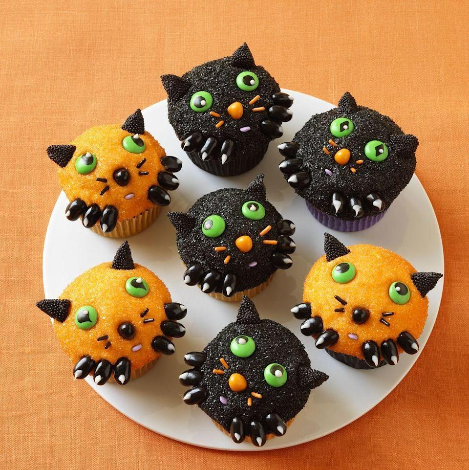 """<p>This treat isn't scary at all! Once you bake your cupcakes, just frost them and dip them in black and orange sanding sugars. Add the little faces with candy.</p><p><a href=""""https://www.womansday.com/food-recipes/food-drinks/recipes/a11375/kitten-cupcakes-recipe-wdy1012/"""" rel=""""nofollow noopener"""" target=""""_blank"""" data-ylk=""""slk:Get the Kitten Cupcakes recipe."""" class=""""link rapid-noclick-resp""""><em><strong>Get the Kitten Cupcakes recipe. </strong></em></a></p>"""