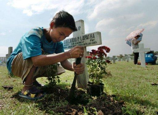 File photo shows a boy cleaning a tomb at a cemetary in Manila during All-Saint's Day. Filipinos who cannot make the traditional All-Saints' Day visits to cemeteries will be able to offer their prayers for the dead online through a website set up by the country's Catholic bishops