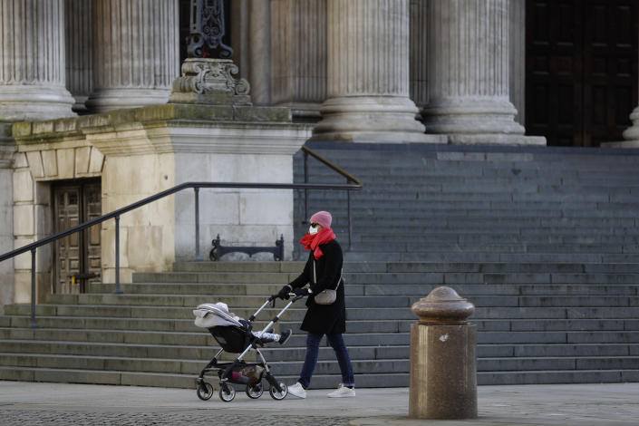 A woman wearing a face mask to curb the spread of coronavirus pushes a child in a buggy past the steps of St. Paul's Cathedral, in the City of London financial district of London, Friday, Jan. 22, 2021, during England's third national lockdown since the coronavirus outbreak began. The U.K. is under an indefinite national lockdown to curb the spread of the new variant, with nonessential shops, gyms and hairdressers closed, most people working from home and schools largely offering remote learning. (AP Photo/Matt Dunham)