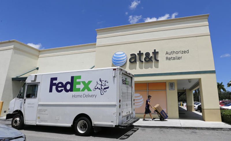 FILE - In this July 27, 2017, shows a Federal Express employee makes a delivery at an AT&T store in Hialeah, Fla. FedEx Corp. reports financial earnings on Tuesday, June 25, 2019. (AP Photo/Alan Diaz, File)