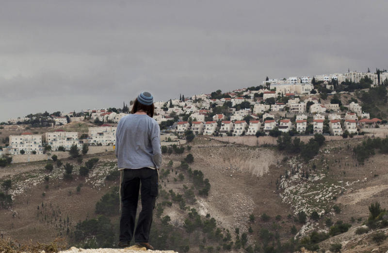 FILE - In this Dec. 5, 2012 file photo, a Jewish settler looks at the West bank settlement of Maaleh Adumim, from the E-1 area on the eastern outskirts of Jerusalem. A leading rights group is accusing Israeli banks of contributing to the expansion of Jewish West Bank settlements by providing loans and mortgages for construction there. In the report, released Wednesday, Sept. 13, 2017, Human Rights Watch called on Israeli banks to extricate themselves from the settlements or face possible action from shareholders. (AP Photo/Sebastian Scheiner, File)