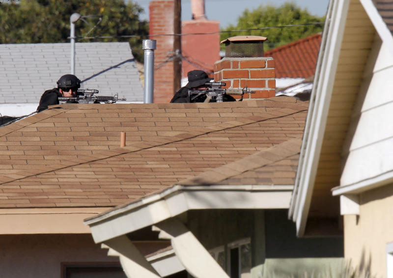 Inglewood police snipers take up a position outside a residence, Wednesday, Nov. 27, 2013, in Inglewood, Calif., where a police officer was shot and another received minor injuries in a confrontation with a gunman who barricaded himself inside a home and could be holding a hostage, authorities said. (AP Photo/Nick Ut)