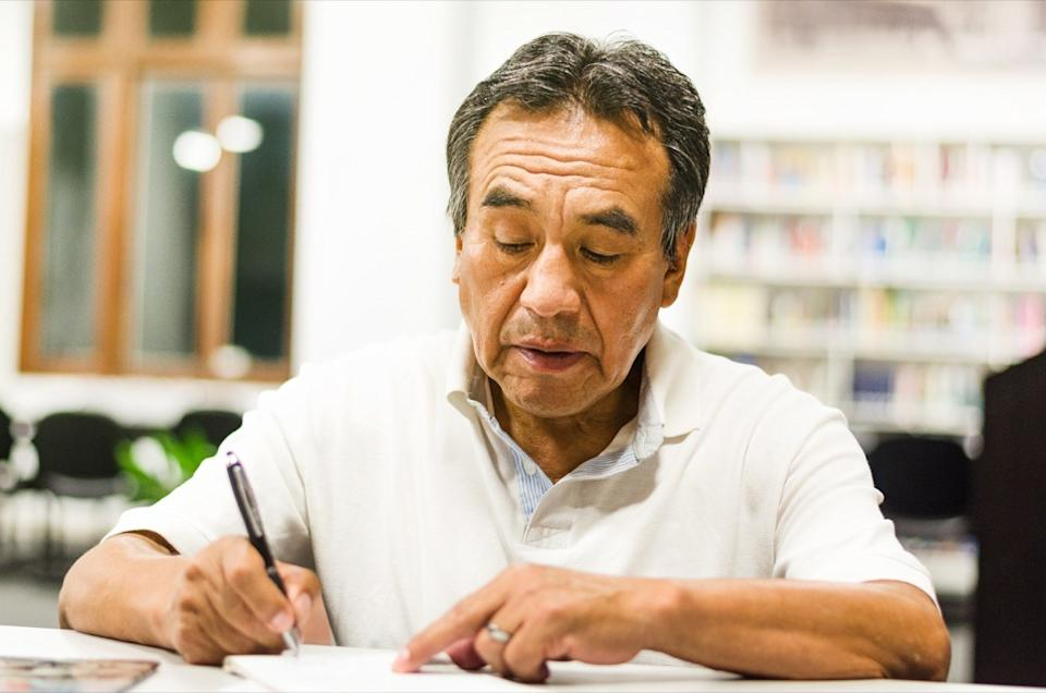 serious senior man sitting on a library bench writing in his book. Senior man sitting in a university classroom.