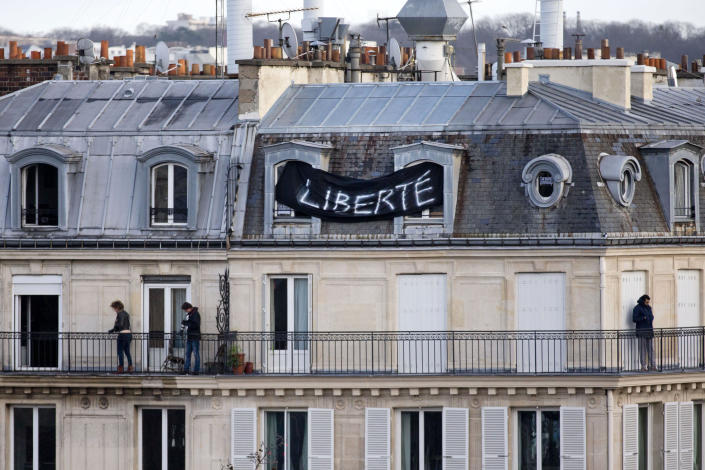 """FILE - In this Jan. 11, 2015 file photo, a banner attached to a house reads """"Freedom"""" as thousands of people gather at Republique Square in Paris. The January 2015 attacks against Charlie Hebdo and, two days later, a kosher supermarket, touched off a wave of killings claimed by the Islamic State group across Europe. Seventeen people died along with the three attackers. Thirteen men and a woman accused of providing the attackers with weapons and logistics go on trial on terrorism charges Wednesday Sept. 2, 2020. (AP Photo/Peter Dejong, File)"""