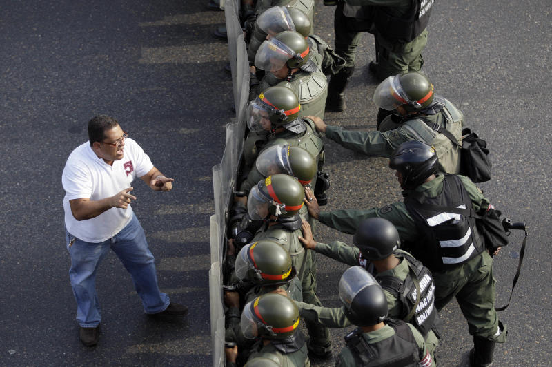An opposition supporter confronts riot police along a highway in the Altamira neighborhood of Caracas, Venezuela, Monday, April 15, 2013. National Guard troops fired tear gas and plastic bullets to disperse students protesting the official results in Venezuela's disputed presidential election. (AP Photo/Fernando Llano)