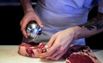 A chef prepares meat in the kitchen of Buenos Aires' Don Julio restaurant