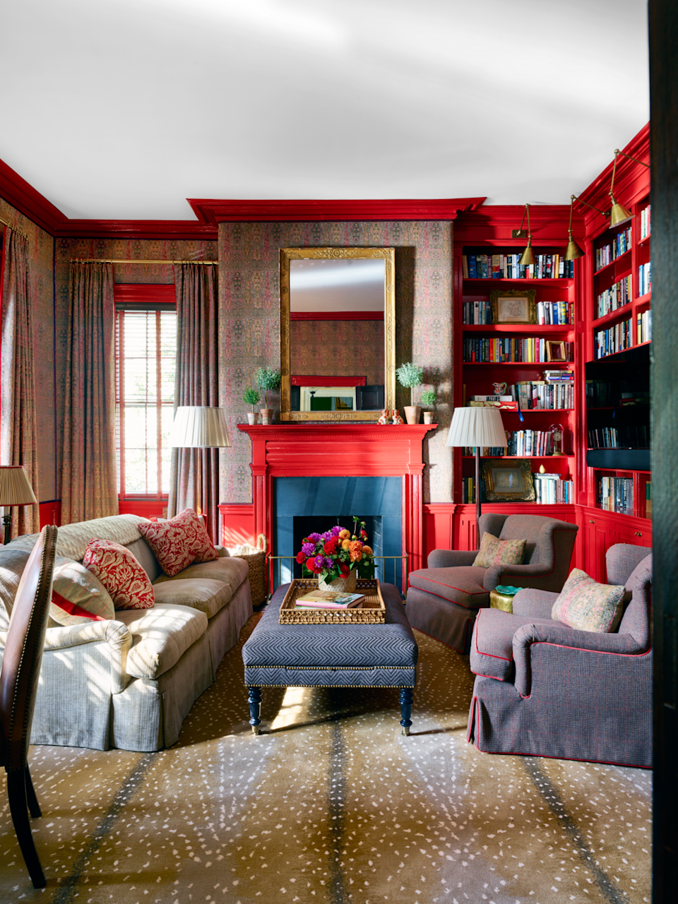 """<p>""""Next year, I believe we'll continue to see the resurgence of rich, saturated hues. From jewel tones, like ruby and sapphire, to earthy shades, like cypress and saffron, designers and homeowners won't shy away from interiors lavishly swathed in color."""" – <a href=""""https://marieflanigan.com/"""" rel=""""nofollow noopener"""" target=""""_blank"""" data-ylk=""""slk:Marie Flanigan"""" class=""""link rapid-noclick-resp"""">Marie Flanigan </a></p><p>Here, designer <a href=""""https://branca.com/"""" rel=""""nofollow noopener"""" target=""""_blank"""" data-ylk=""""slk:Alessandra Branca"""" class=""""link rapid-noclick-resp"""">Alessandra Branca</a> marries a creamy, lively red with a pop of blue from the fireplace and a mix of muted colors to create an energizing yet cozy space for cocktails and conversation. </p>"""