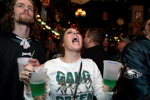 Football fans, Nicholas Breslin (L) and Laura Demutis, react as they watch Super Bowl LII between the New England Patriots and the Philadelphia Eagles at the city's oldest tavern, McGillin's Olde Ale House in Philadelphia, Pennsylvania, U.S. February 4, 2018. REUTERS/Jessica Kourkounis