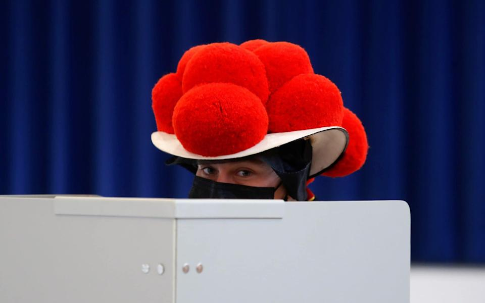 A woman wearing traditional Black Forest costume votes in Gutach, in the Black Forest, Germany, September 26, 2021. REUTERS/Arnd Wiegmann - ARND WIEGMANN /REUTERS