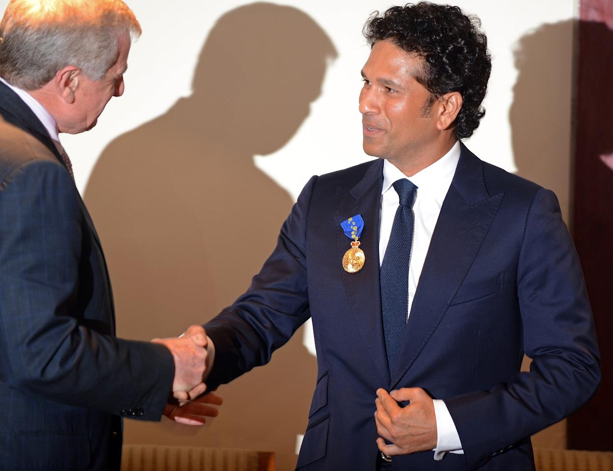 """Simon Crean (L), Australian Minister for Regional Australia, Regional Development and Local Government, shakes hands after presenting the membership of The Order of Australia to Indian cricketer Tendulkar in Mumbai on November 6, 2012. India's record-breaking batsman Sachin Tendulkar on November 6 was conferred with membership of the Order of Australia. Australian Prime Minister Julia Gillard, who announced Tendulkar's membership to the Order during a three-day state visit to India last month, told reporters that Tendulkar deserved the """"special honour"""" because he was a """"very special cricketer"""". AFP PHOTO/ INDRANIL MUKHERJEE"""