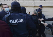 Members of a far-right organization and police remove man from a church where they were protesting church support for tightening Poland's already restrictive abortion law in Warsaw, Poland, Sunday, Oct. 25, 2020. Poland constitutional court issued a ruling on Thursday that further restricts abortion rights in Poland, triggering four straight days of protests across Poland.(AP Photo/Czarek Sokolowski)