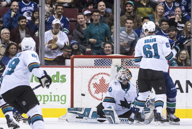 The puck bounces off the post behind San Jose Sharks goalie Aaron Dell and stays out of the net as Justin Braun (61) watches during the third period of the team's NHL hockey game against the Vancouver Canucks on Saturday, March 17, 2018, in Vancouver, British Columbia. (Darryl Dyck/The Canadian Press via AP)