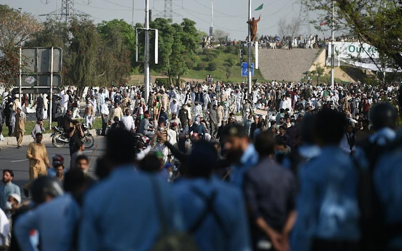 Pakistani policemen look on as supporters of executed Islamist Mumtaz Qadri gather on a main road during an anti-government rally in Islamabad on March 27, 2016 (AFP Photo/Farooq Naeem)