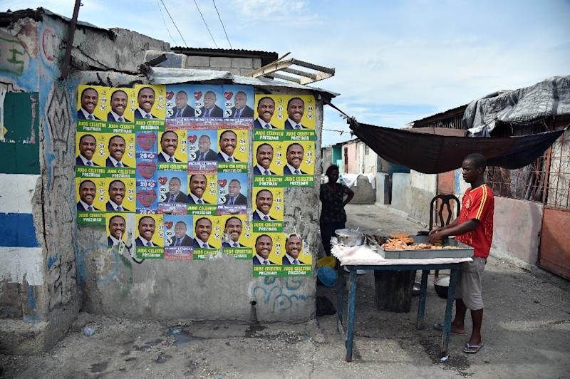 A man sells food close to electoral posters of presidential candidate Jude Celestin of the LAPEH party, in Port-au-Prince, Haiti, on October 22, 2015 (AFP Photo/Hector Retamal)