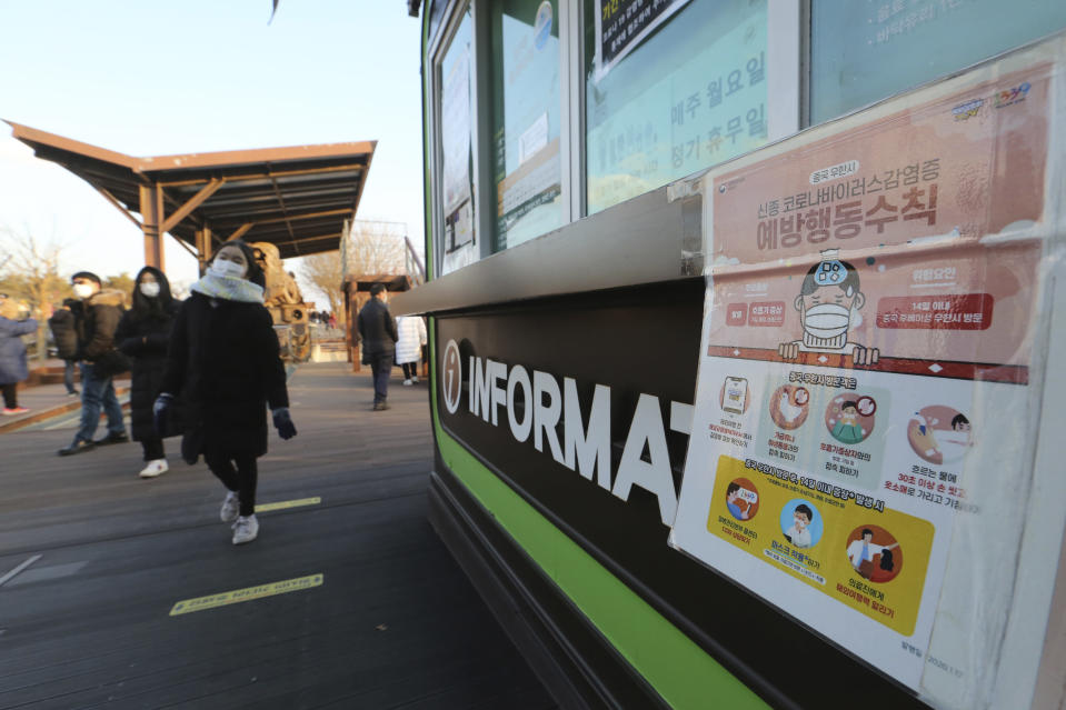 "People wearing face masks pass by a poster about precautions against the coronavirus as they visit to celebrate New Year at Imjingak in Paju, near the border with North Korea, South Korea, Friday, Jan. 1, 2021. The poster reads: ""Precautions against the coronavirus."" (AP Photo/Ahn Young-joon)"