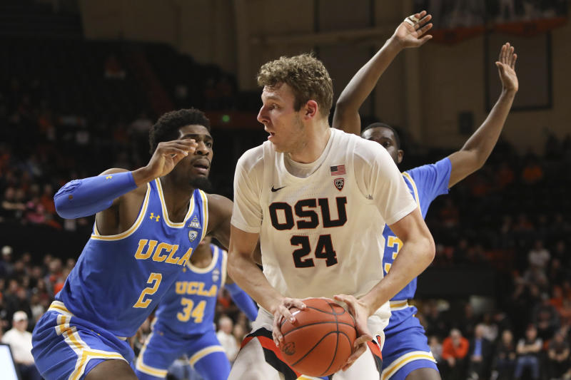 UCLA's Cody Riley (2) and Prince Ali (23) defend against Oregon State's Kylor Kelley (24) during the first half of an NCAA college basketball game in Corvallis, Ore., Thursday, Jan. 23, 2020. (AP Photo/Amanda Loman)