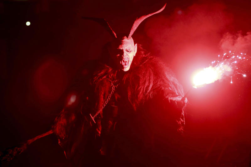 FILE - In this Saturday, Dec. 1, 2018, file photo, a man dressed as the pagan character Krampus screeches at spectators during a traditional Krampus run in Hollabrunn, Austria. On Friday, Dec. 13, 2019, The Associated Press reported on a video circulating online incorrectly described as showing migrants trying to disrupt a parade of St. Nicholas in Austria and being rebuffed by men dressed as Krampus. In the statement, the organizers say that the people seen in the video are not migrants but locals wearing padded clothing who volunteered to provoke the Krampus characters. (AP Photo/Ronald Zak)